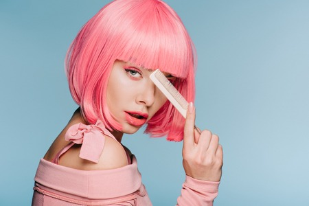 beautiful stylish girl in pink wig posing with hair comb isolated on blue Фото со стока - 117877571