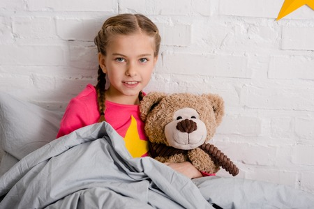 Curious kid with braids holding teddy bear in bed Stockfoto