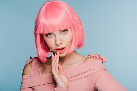surprised young woman gesturing and posing in pink wig isolated on blue Stockfoto