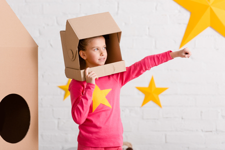 Inspired kid in pink clothes and cardboard helmet holding fist up Stock Photo