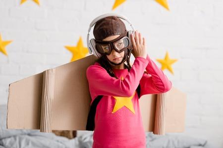 Sad child in flight helmet and goggles listening music in headphones