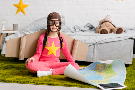 Cute kid in flight helmet sitting on carpet with map Фото со стока - 117867064