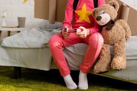 Cropped view of child with teddy bear holding gamepad on bed