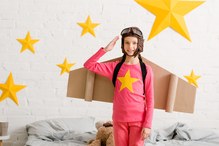 Adorable kid with cardboard wings saluting with smile
