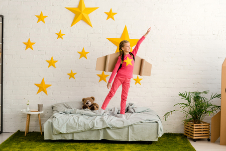 Blissful kid with cardboard wings standing on bed with hand up