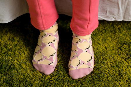 Partial view of child in funny socks standing on green carpet 版權商用圖片