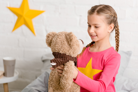 Blissful kid with braids looking at teddy bear with smile 스톡 콘텐츠