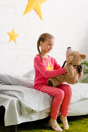 Cute kid with braids sitting on bed and looking at teddy bear