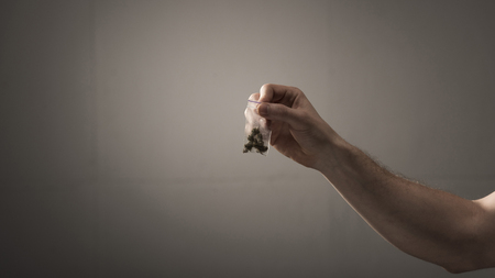 partial view of man holding pack with marijuana on grey background