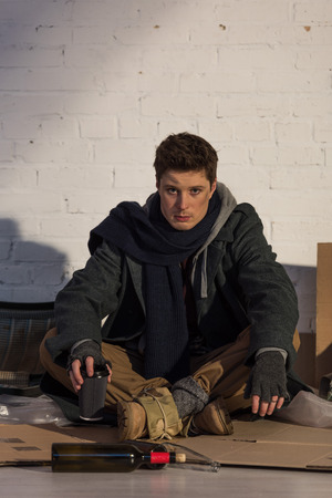 homeless man sitting on cardboard by white brick wall and holding paper cup