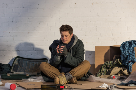 poor homeless man drinking from paper cup while sitting on cardboard surrounded by messed rubbish