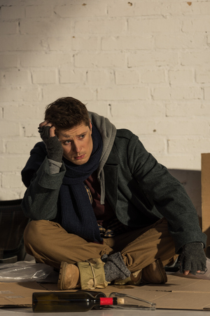 depressed homeless man sitting on cardboard and propping head with hand