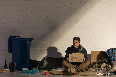 depressed homeless man sitting on cardboard surrounded by garbage and holding cardboard card with