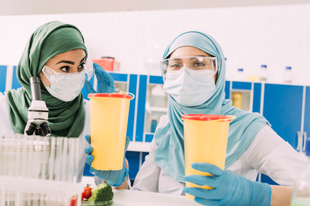 female muslim scientists holding clinical waste containers and looking at camera in chemical laboratory Stock Photo