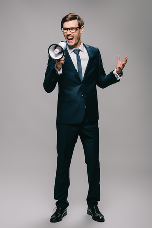 angry businessman in suit screaming in megaphone isolated on grey Stock Photo