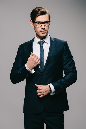 handsome businessman touching jacket on grey background