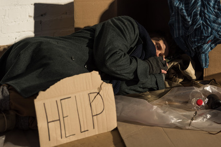 depressed homeless man lying on cardboard on rubbish dump