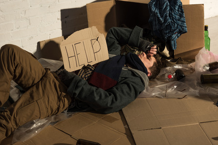homeless man lying on cardboard on rubbish dump and holding card with help inscription
