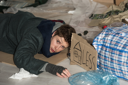 despaired homeless man lying on cardboard in rubbish dump, with symbol of house and