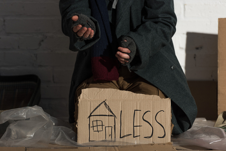 partial view of begging man with symbol of house and less inscription on cardboard card