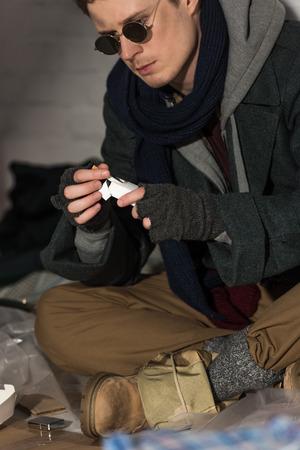 homeless man in dark glasses getting cigarette from pack