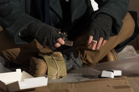 partial view of homeless man in fingerless gloves holding lighter and cigarette