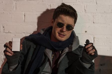 homeless man in dark glasses and fingerless gloves holding cigarette pack Stock Photo