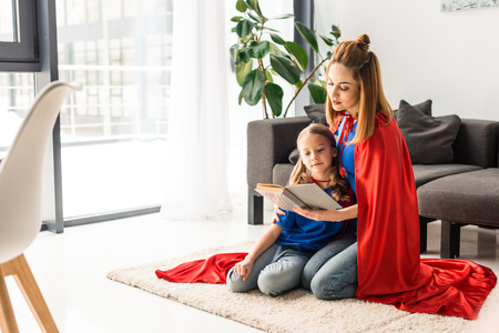 daughter and mother in red cloaks sitting on floor and reading book