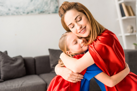 kid and mother in red cloaks hugging and smiling at home