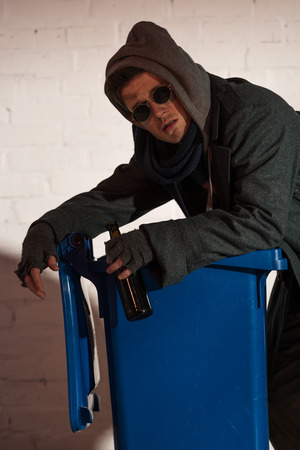 homeless man with alcohol bottle leaning on trash container
