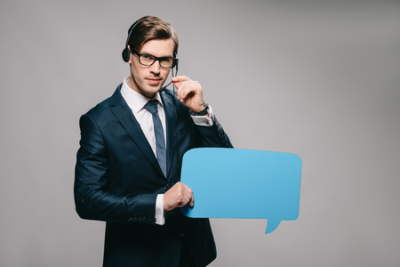 serious man in suit wearing headset and holding speech bubble on grey background Stock fotó