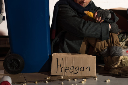 cropped view of homeless man sitting near trash container and holding corn cob