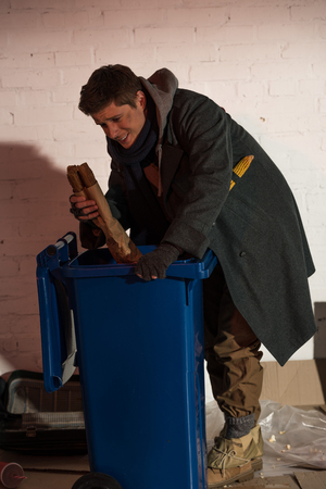 hungry homeless man getting bread baguette from trash container