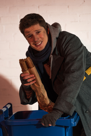happy homeless man holding bread baguette while standing by trash container Stock Photo