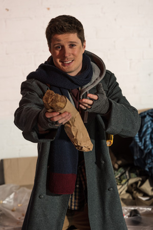 homeless man holding bread baguette in stretched hand Stock Photo