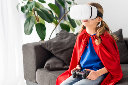 Cute kid in red cloak and virtual reality headset playing video game 免版税图像