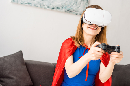 Mother in red cloak and virtual reality headset playing video game