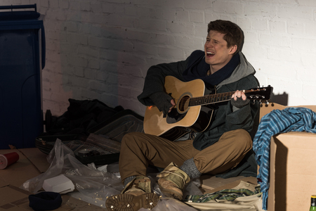 homeless man playing guitar and singing while sitting on rubbish dump