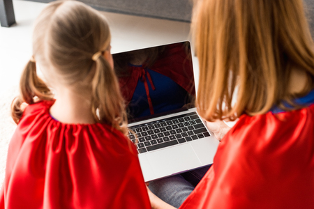 Back view of mother and daughter in red cloaks looking at laptop screen Stock Photo