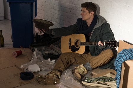 homeless man with guitar sitting on rubbish dump and holding hat in stretched hand