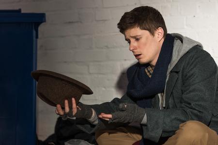 homeless beggar man holding hat white sitting by white brick wall on street