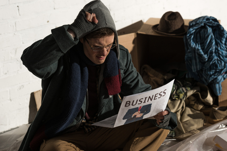 affected homeless man reading business newspaper while sitting surrounded by rubbish Stock fotó