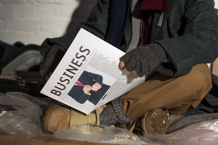 cropped view of man in fingerless gloves holding business newspaper