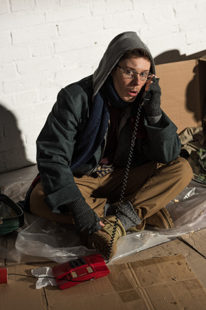 homeless man in hood and glasses grimacing while using vintage phone