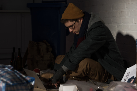 homeless man using laptop while sitting on rubbish dump Stock Photo
