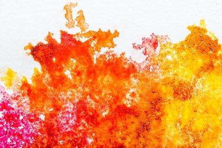 top view of orange and yellow watercolor spills on white background