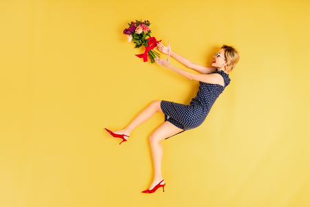 Cheerful young woman in dress posing with flowers on yellow background
