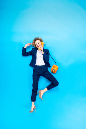 Elegant woman in suit and high-heeled shoes talking on telephone on blue background Stock Photo