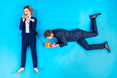 Man dialing number while woman talking on telephone on blue background