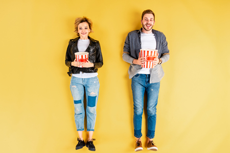 Smiling couple in jeans holding popcorn on yellow background